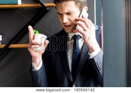 Nervous conversation. Angry young bearded man is expressing negativity while talking on the mobile phone. He is standing in office and holding cup of coffee while gesticulating irritably