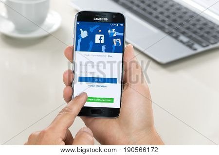 Krynica Poland - June 10 2017: Samsung Galaxy S7 in the hand when logging into Facebook applications. Facebook is largest and most popular social networking service in the world.