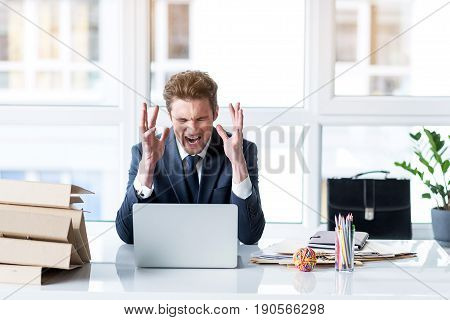 Detest my job. Portrait of young angry businessman is working on laptop in office. Screaming man is expressing hate and wrath