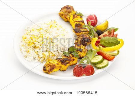 High angle view of grilled chicken kebab on a simple plate. Called chelo joojeh in Persian cuisine as it is served with rice. Studio shot over a clean white table top. Fusion food barbecue concept.