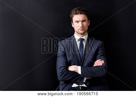 Serious business intentions. Waist up portrait of elegant young man in suit is keeping arms crossed and looking at camera with concentration. copy space in the left side