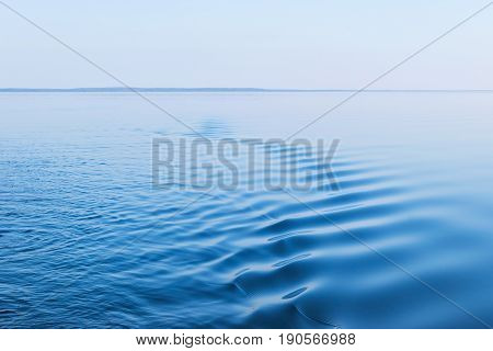 Motor boat leaves small waves behind boat in the blue sea. Evening view of sea bay at sunset