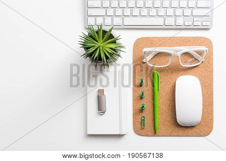 Necessary stuff. Close up top view of keyboard and glasses are on table with houseplant and other supplies on white background. Copy space in the left side