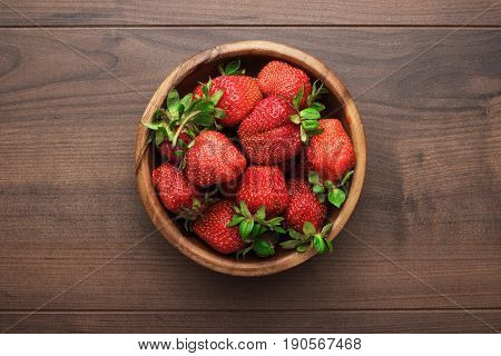 bowl full of fresh strawberries. strawberries on the brown table. wooden bowl with ripe straberries. bowl of strawberries on wooden background