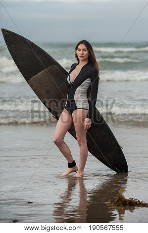 Sexy California surfer girl holding black surf board standing on reflection in moving water.
