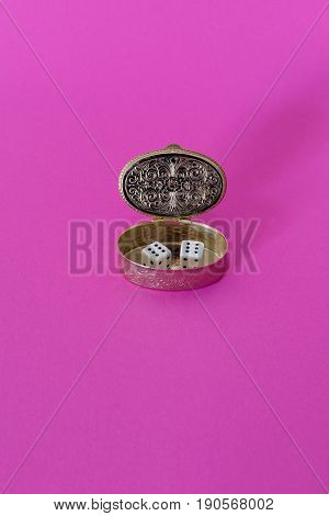 A little box with two dice in it on a pink background