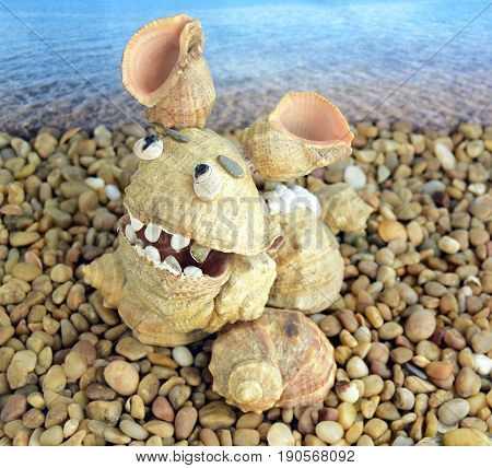 The dinosaur is made of sea cockleshells. An object is located on the beach.