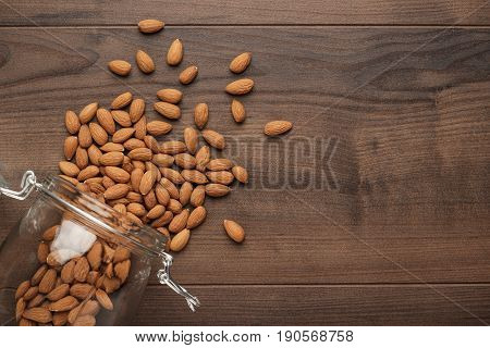 overturned glass jar full of almond seeds. many almond almond seeds background. almond seeds on wooden back. photo of overturned glass jar of almond seeds with copy space
