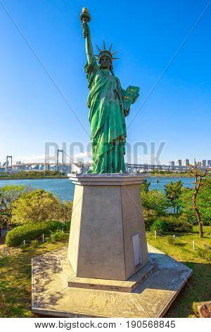 Urban landscape of Statue of Liberty and Rainbow Bridge, icons of Odaiba Island in Tokyo, Japan. Replica of famous Statue of Liberty of New York. Tokyo cityscape on background. Vertical shot.