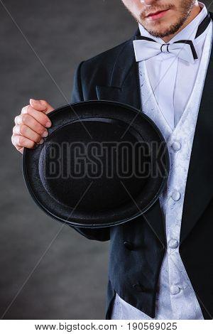 Tuxedo male fashion classical look concept. Elegantly dressed man holding black fedora hat. Studio shot on dark background