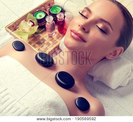 Massage and body  care. Spa body massage treatment. Woman having massage in the spa salon for beautiful girl . hot stone massage