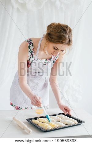 Young beautiful woman preparing homemade croissants. Housewife lubricate croissants egg and sprinkle with sugar. The concept of home cooking. Toning.
