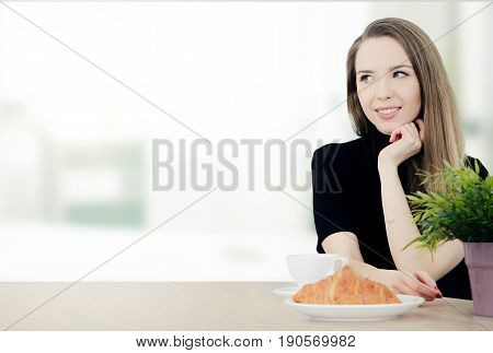 Woman sitting at a table with coffee and croissant. woman beautiful young sitting smiling table croissant cup copy space your text concept