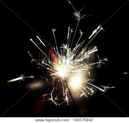 A burning sparkler on a black background