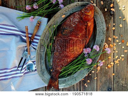 smoked bream on a silver platter with onions and chips