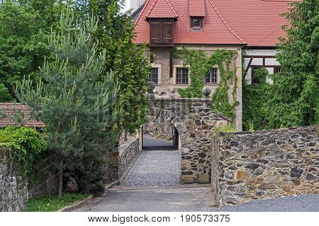 The photo shows Czocha Castle, located in the village of Leśna in south-western Poland. In the foreground, we see a chateau road with paving stones. On both sides is bounded by a stone wall. It passes under an arched gate. In the distance you can see cast