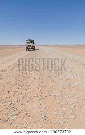 Land Cruiser 4x4 on empty rocky desert road to Erg Chebbi in the Moroccan Sahara, Africa.