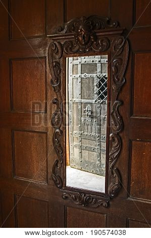 Photo shows an old mirror having a wooden frame. The frame is carved. At the top, there is an image of the human head above the door frame. It is placed on a wall of wooden paneling. It is an architectural element of the castle of Czocha in the village of