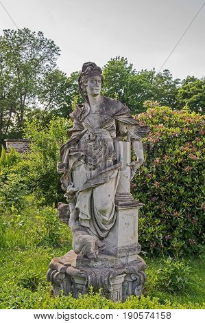 The photo shows an old stone statue of a woman. The statue is covered with a black coat. It stands on a stone stump among green plants. Behind the blooming rhododendrons. They are made of antique robes. They are an architectural element of the castle of C