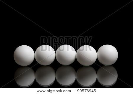 Five balls for ping pong in a row, on a dark background