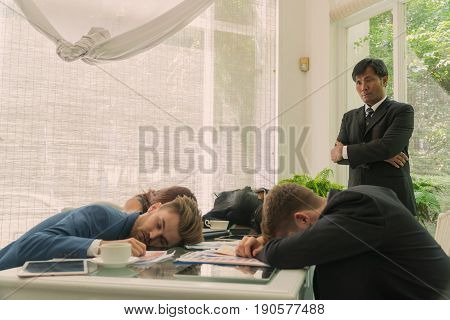 Group of business people sleeping on the table with the head stand with a look of displeasure.