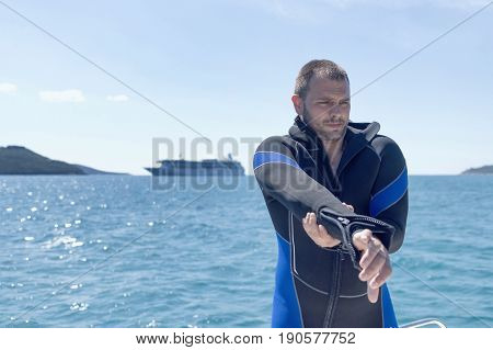 Scuba Diver On Boat, Putting On His Wetsuit.