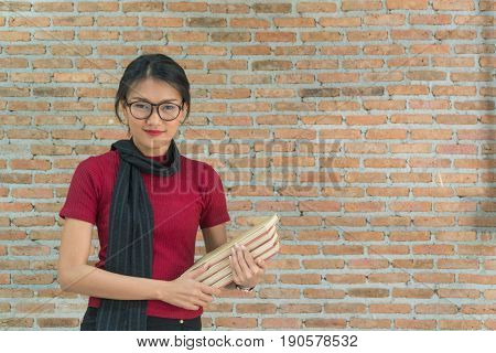 Asian beautiful young woman standing holding book with brick wall as background.
