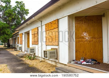 Abandoned Units With Trash & Boarded Up Windows & Doorways