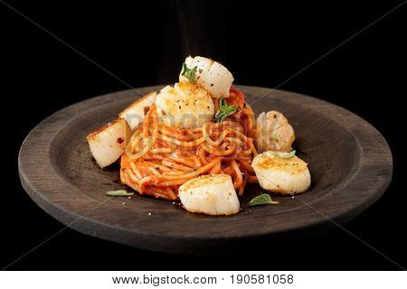 Pasta with fried scallops, oregano and tomato sauce on wooden plate isolated on black background