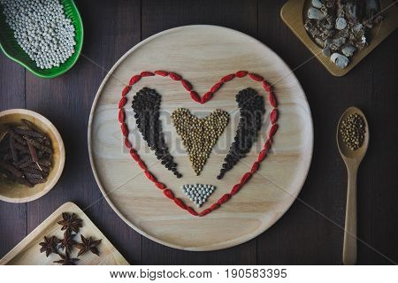Spices and herbs in wooden Plate and wooden spoons with heart concept. Food and cuisine ingredients.