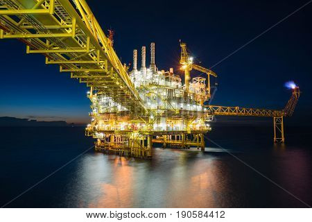Offshore oil and gas central processing platform in sun set where produced raw gases and treat then sent to onshore refinery, petrochemical and power generation plant. Energy business in Thailand.