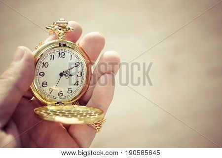 Golden pocket watch in hand close up. (Processed in sepia colour tone)