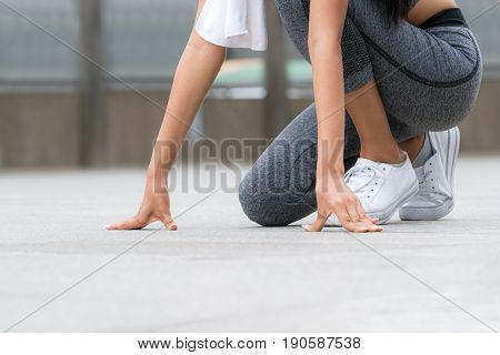 Woman runner in starting run position ready to start running. Concept of woman sports running.