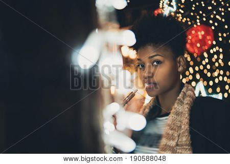 Portrait of young cute curly afro american girl surrounded by night city New Year or Christmas lights garlands and decoration she is vaping electronic cigarette with copy space for text or logo