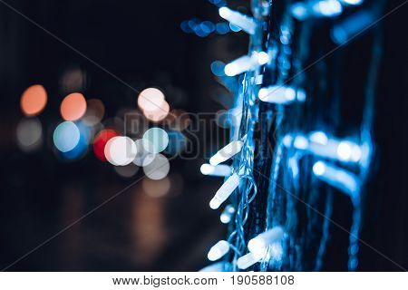 Glowing New Year or Christmas garland decoration around city tree with shallow depth of field and multiple bokeh of city lights in the blurred background with copy space for text your logo or advert