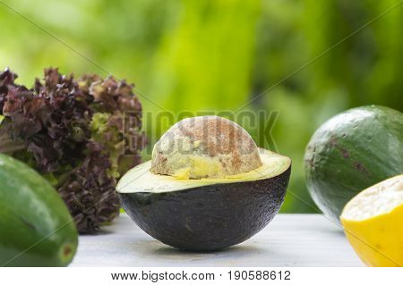 Avocado and avocado pieces on a wooden floor and has a background of nature; Selected focus