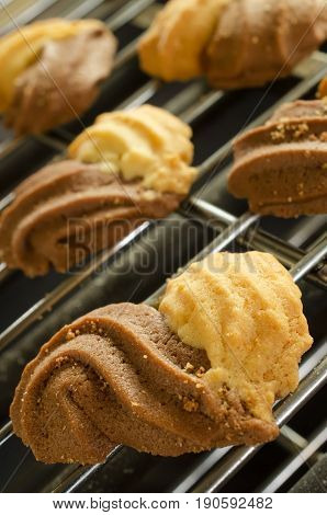 Freshly baked cookies in the shape of a heart on a tray rack. Closeup with extremely shallow.