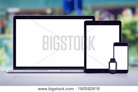 Responsive design mockup of laptop, tablet, smartphone and smartwatch on office desk.