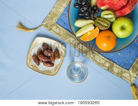 A top view of an Iftar break fast spread consists of dates and assorted fresh fruits. A healthy and nutritional meal during holy month of Ramadan.