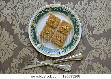 Traditional arabic dessert recipe - Basbousa cake, arranged on a decorative plate. Middle eastern dessert recipes.