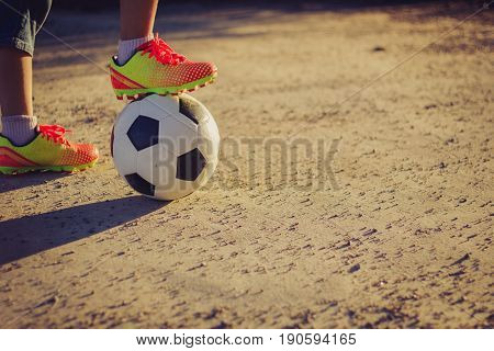 Little boy in shorts and trainers with his foot resting on top of a soccer ball