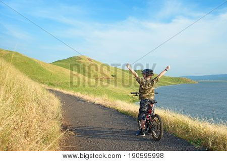 Happy boy with open arms riding his bike in the hills, enjoying sunny day, beautiful trail winding ahead through the bay.