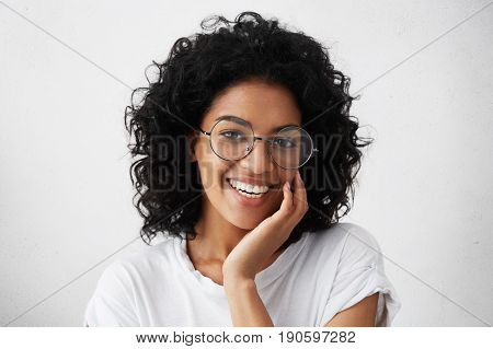 Close-up Portrait Of Afro American Woman With Dark Curly Bushy Hair Wearing Glasses And White Top Ho