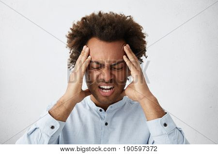 Stressed Mixed Race Man With Head Of Curly Hair Frowning His Face Holding Hands On Head Having Depre