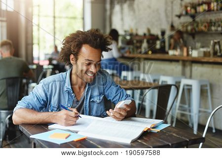 Image Of Stylish African Student With Earring Wearing Denim Shirt Sitting At Wooden Table Doing His
