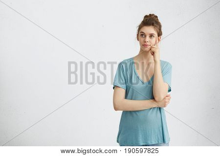 Blue-eyed Woman With Fair Hair Wearing Long Loose Blue T-shirt Having Pensive Expression Thinking Ov