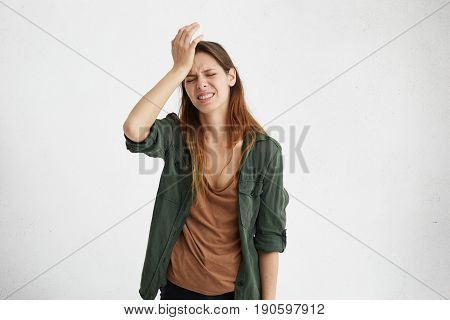 Frustrated Brunette Woman Wearing Casual Clothes Holding Hand On Forehead Being Depressed Regreting