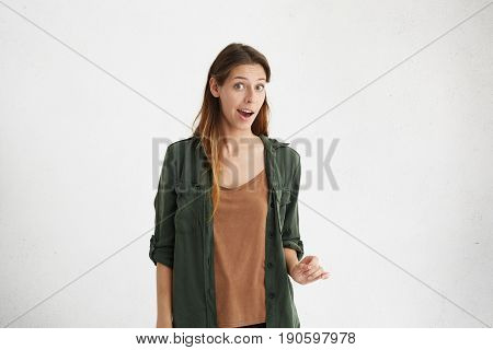 Good-looking Young Woman Dressed Casually Looking With Distrust And Wonder Into Camera. Female With