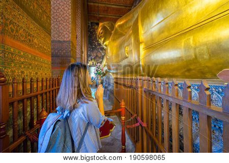 Young woman traveler with backpack respecting or pray at reclining buddha in Wat Pho at Bangkok Thailand. Traveling in Bangkok Thailand
