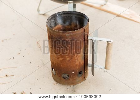 Rusty old chimney starter for igniting charcoal briquettes.